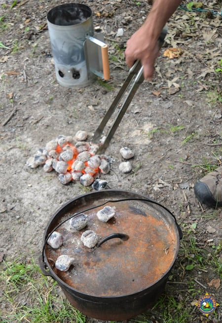hot coals being place on the lid of a Dutch oven out at a campground
