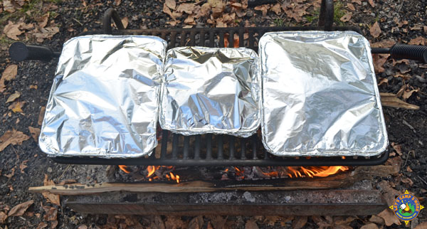 3 pans of nachos over the campfire