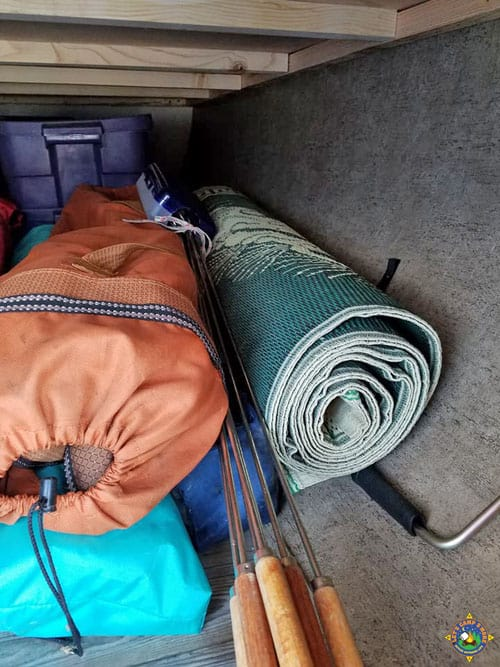 RV storage compartment filled with camping gear
