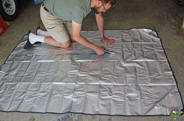 man cutting a solar blanket into two pieces