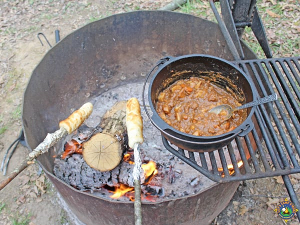 stew and rolls being cooked over a campfire
