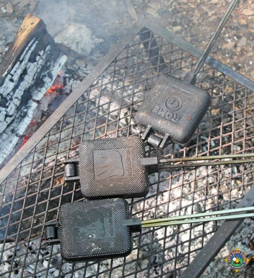 3 pie irons on a grate over a campfire
