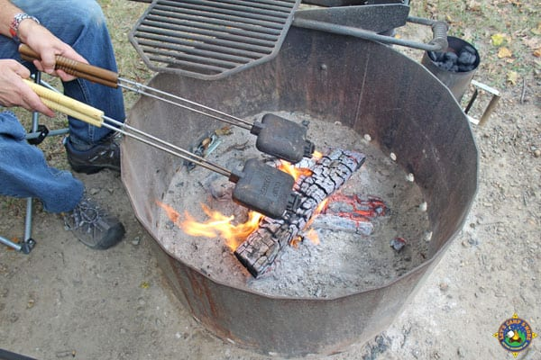 man holding 2 pie irons over a campfire ring