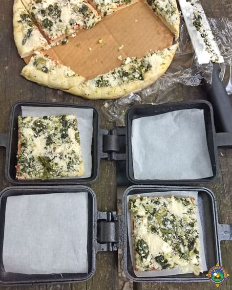 slices of pizza being put into pie irons to cook over the campfire
