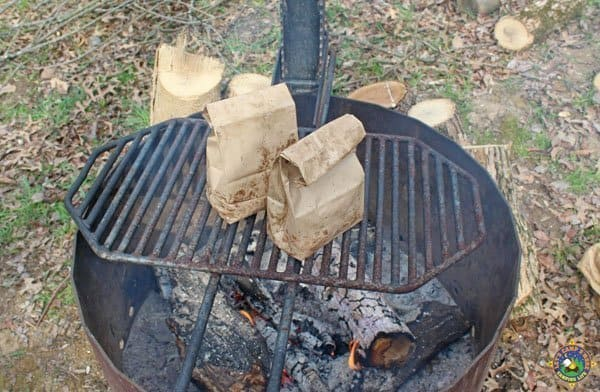 2 paper lunch sacks filled with eggs and bacon being cooked over the campfire