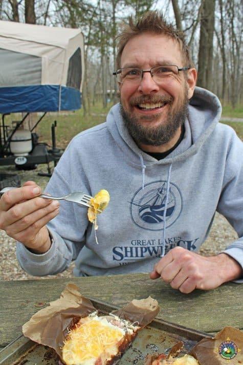 smiling man enjoying a camping breakfast