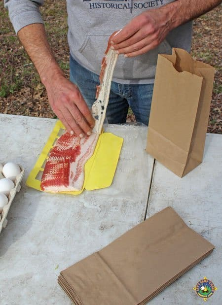 man pulling a piece off a package of bacon
