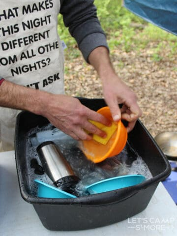 a wash basin of camping dishes being done
