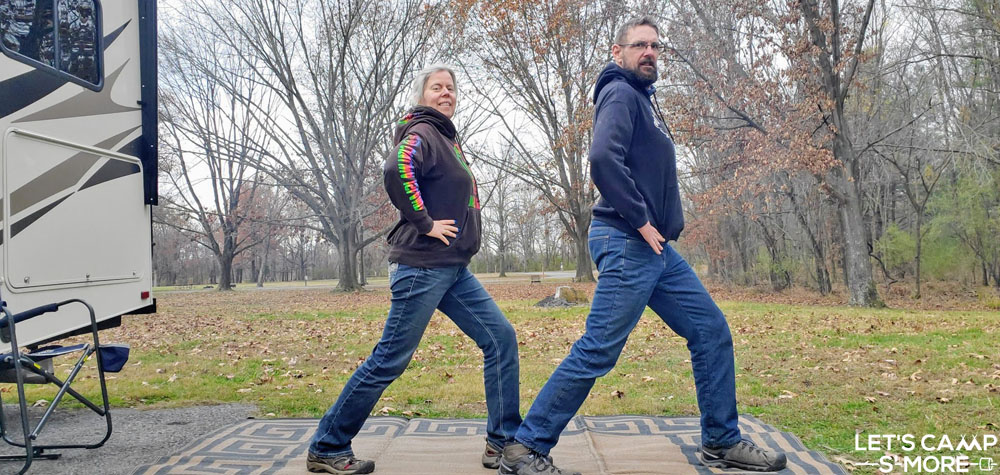 a couple doing lunges for exercise while camping