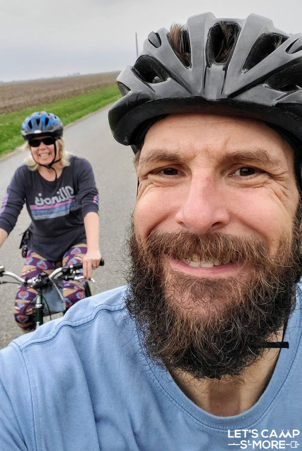 selfie of a couple riding bikes for exercise while camping
