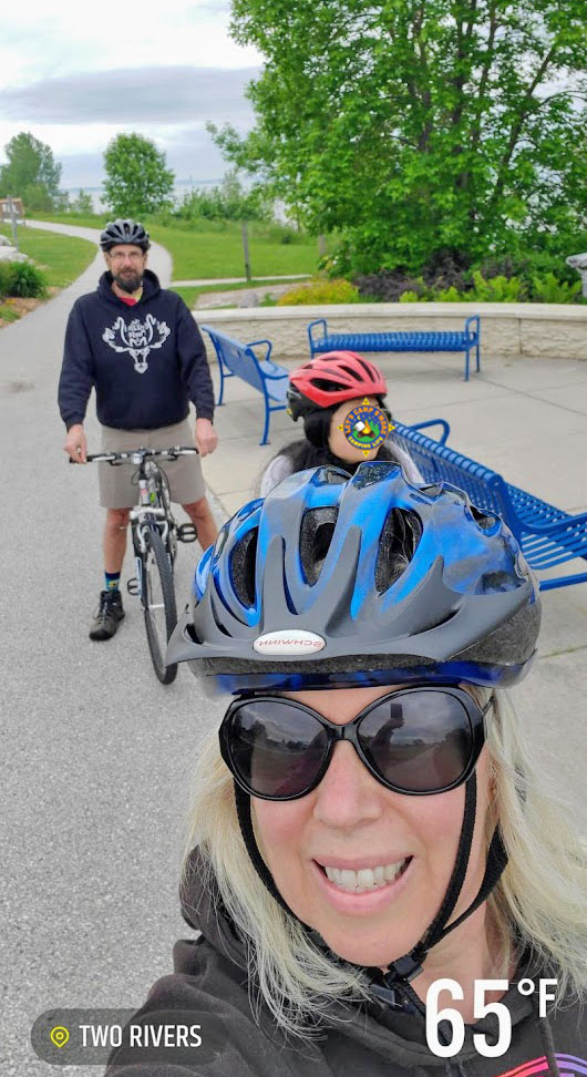 a family riding bikes along a path next to Lake Michigan in WIsconsin