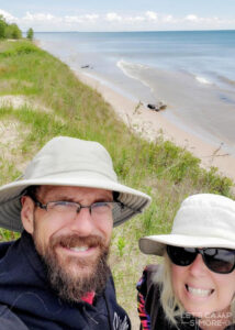 couple pausing to take a selfie while walking along the edge of Lake Michigan
