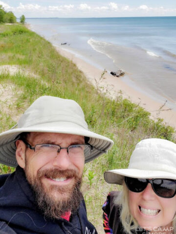 couple pausing to take a selfie while walking along the edge of Lake Michigan