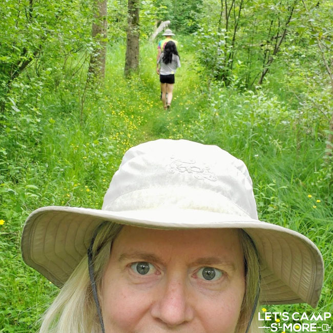 woman taking a selfie with her family walking through the woods in the background