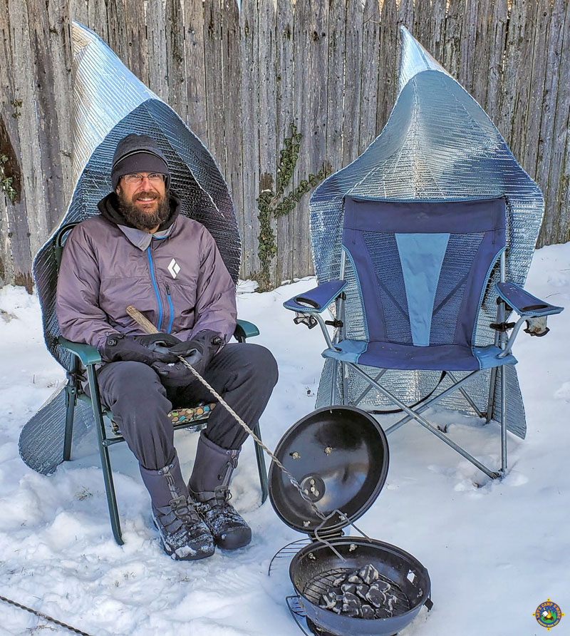 two camping chairs with fire reflectors attached to them next to a campfire out in the snow with a man sitting in one of the chairs