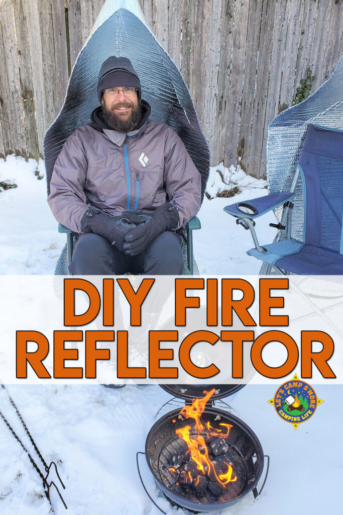 man sitting next to campfire in a camping chair with a fire reflector attached to it keeping warm