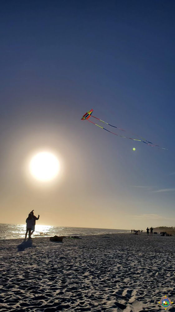 people flying a kite on the Gulf beach in Alabama