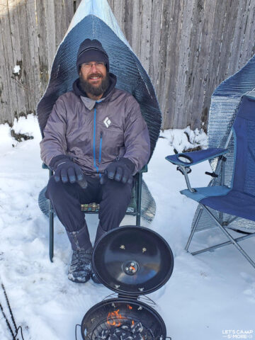 happy camper man staying warm next to a campfire with a campfire reflector