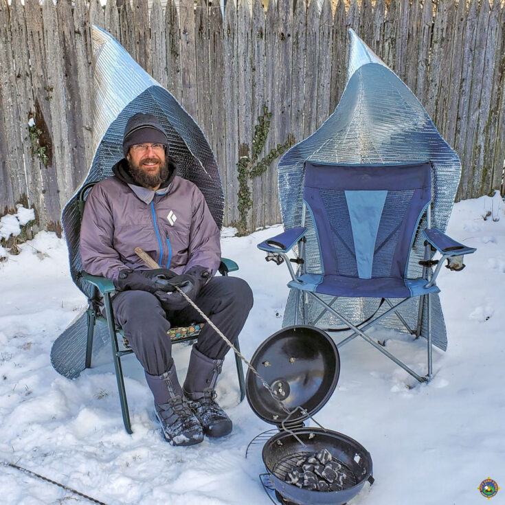 man keeping warm next to campfire in a camping chair with a fire reflector attached