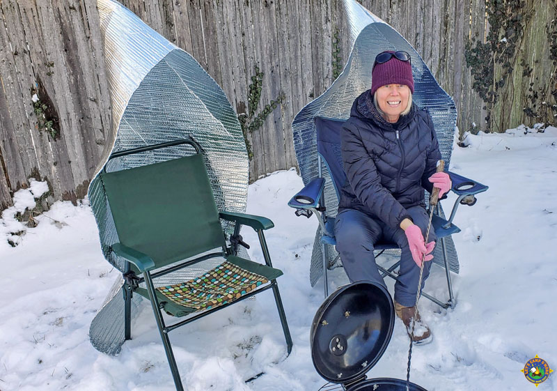 woman sitting outside in the snow in a camping chair with a heat shield on it next to a campfire
