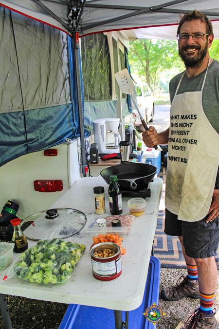 smiling man cooking outside a pop-up camper while camping