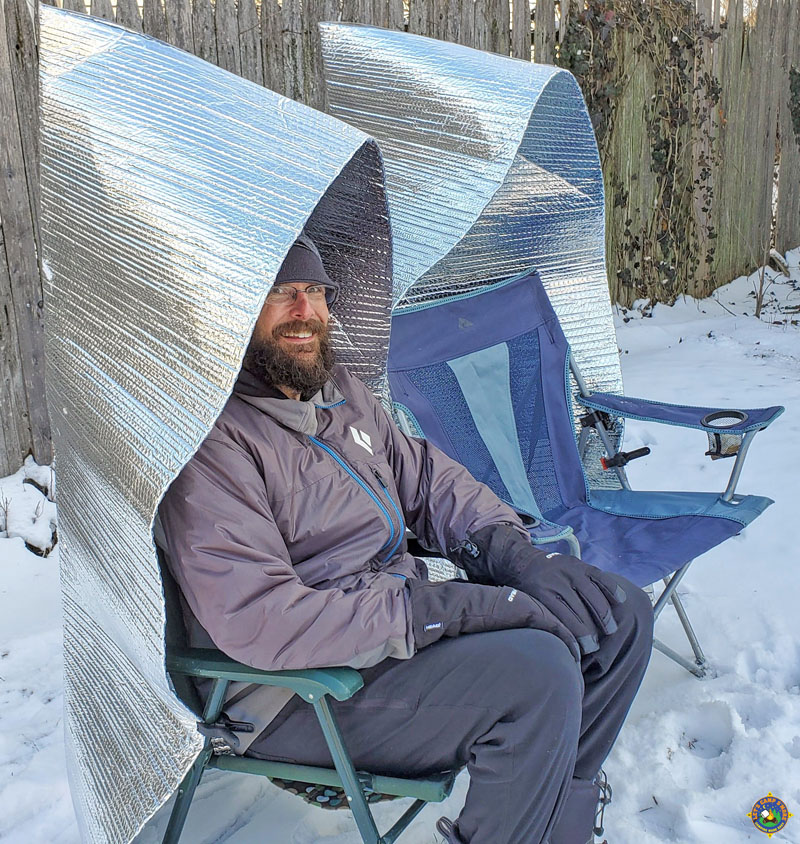 man sitting outside in the snow in a camp chair with a campfire reflector on it
