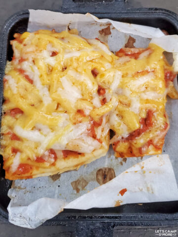 close up of a piece of cheese pizza that was baked over the campfire