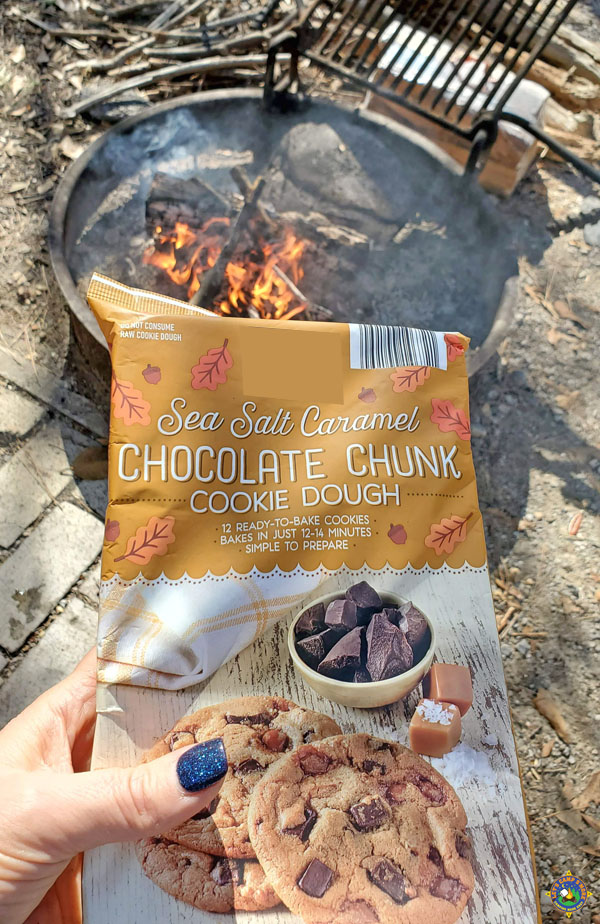 a package of caramel chocolate chunk cookie dough behind held with a campfire in the background
