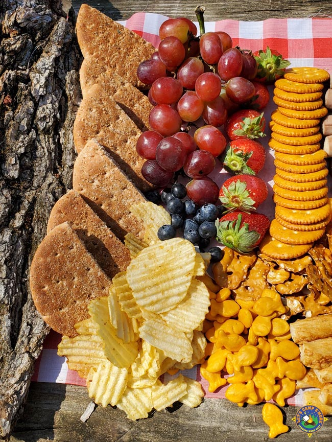 Fruits, crackers, chips, and bread on a charcuterie board