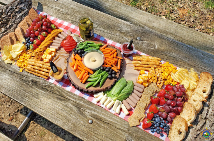 overhead view of a charcuterie board on a picnic table