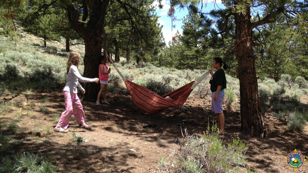 4 kids playing with a hammock while camping
