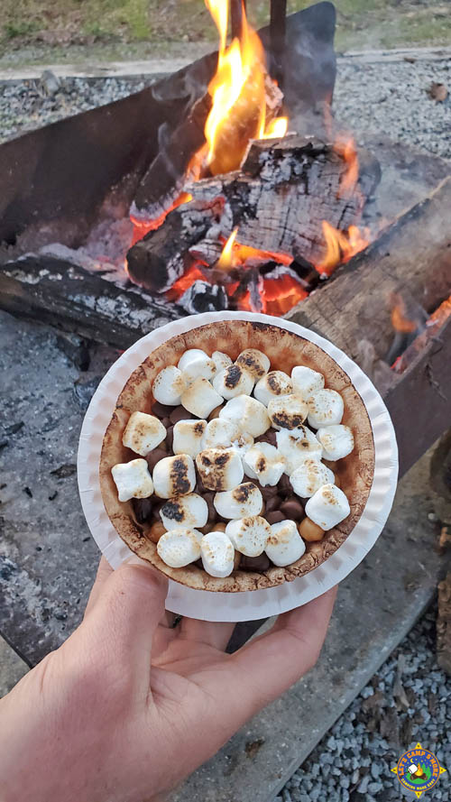 hand holding a s'more banana waffle bowl in front of a campfire