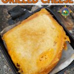 close up of a campfire grilled cheese sandwich in a pie iron