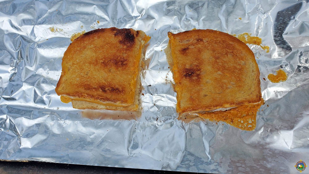 2 sandwiches being grilled on foil over a campfire
