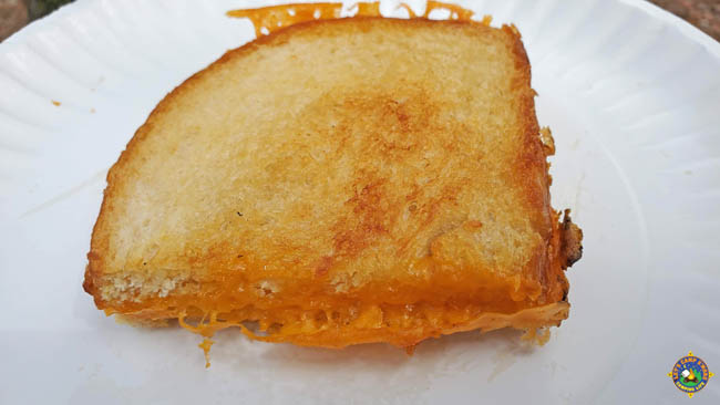 close up of a perfectly grilled cheese sandwich on a paper plate