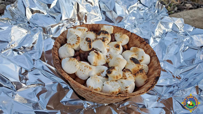 a waffle bowl filled with s'more fixings laying on a piece of foil