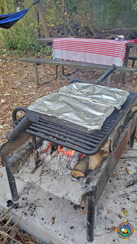 pans of campfire pizza foil pans cooking over a campfire