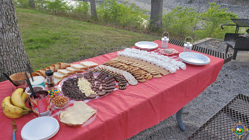side view of a dessert buffet on a picnic table at a campground