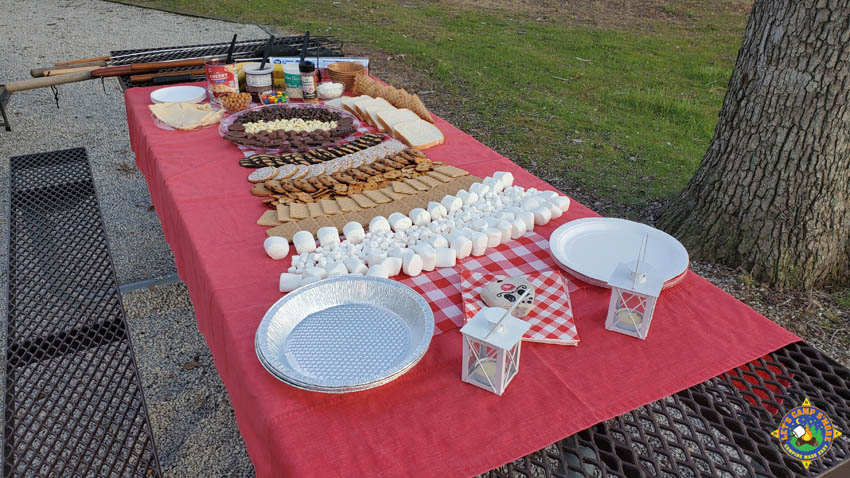s'more charcuterie board set up on a picnic table at a campground