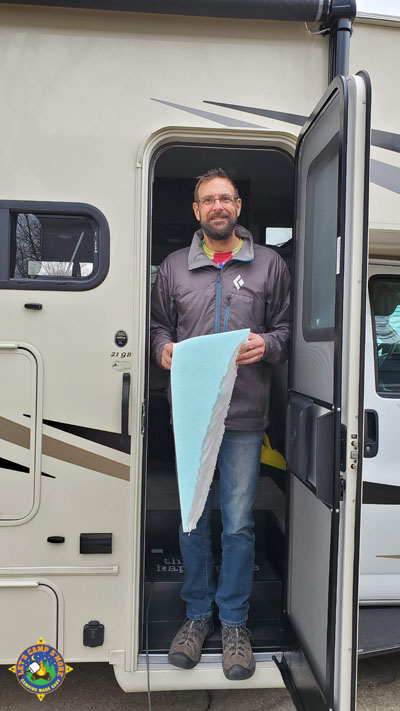 man standing the doorway of a motorhome holding a piece of foam