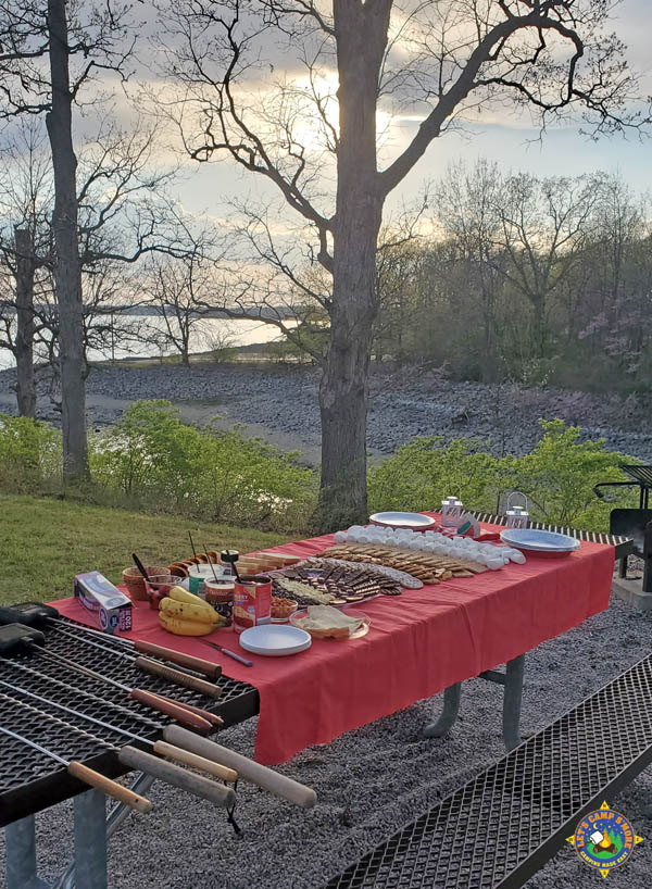 picnic table with s'mores ingredients spread out on top