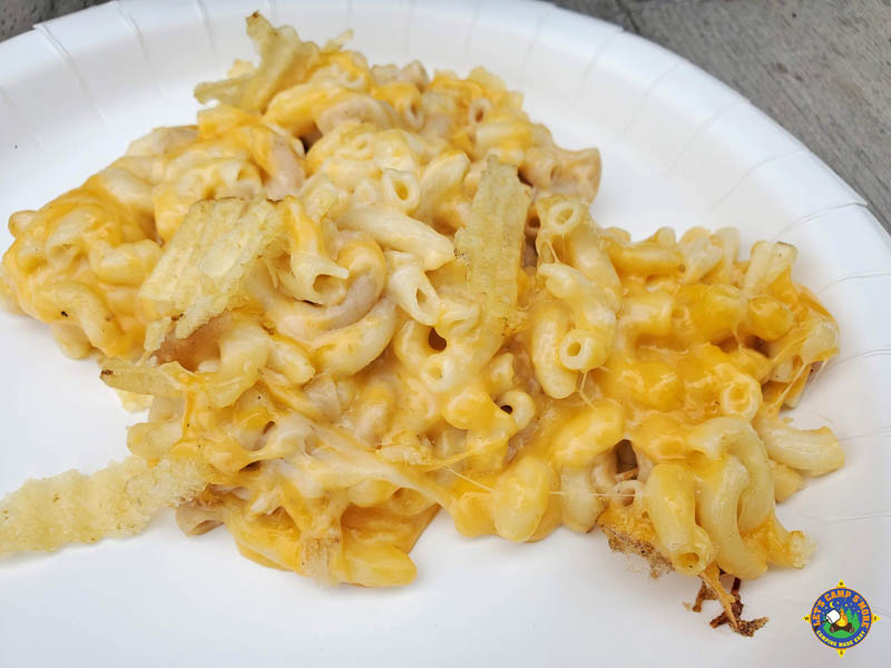 close up of a serving of macaroni and cheese on a white paper plate