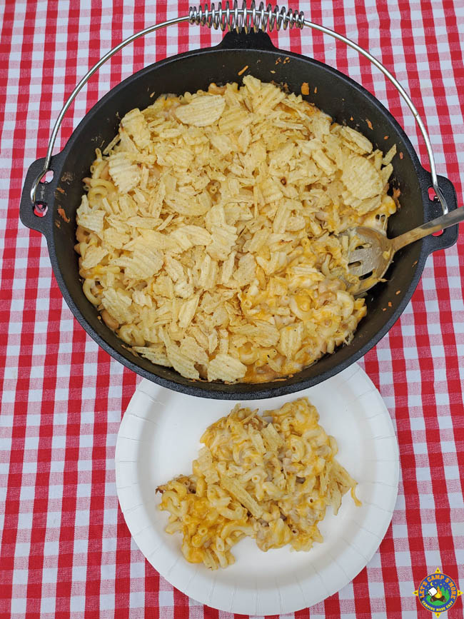 Dutch Oven with Macaroni and Cheese and a white plate with a serving on it on top of a red checkered tablecloth