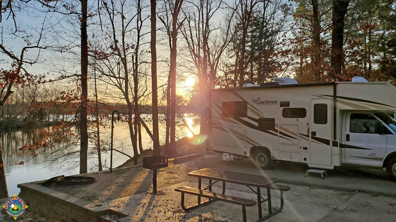 sunrise over a lake with a motorhome parked at a campground