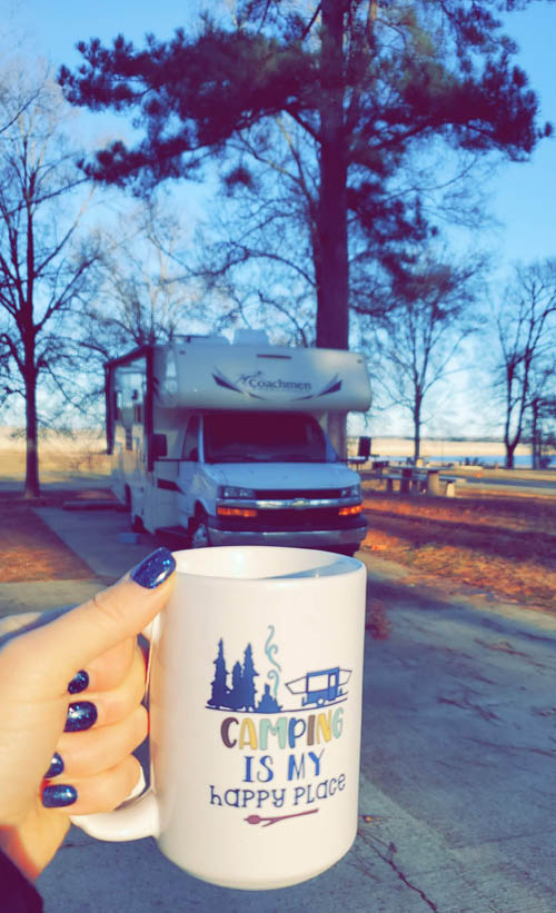 camping is my happy place mug being held in front of a parked motorhome