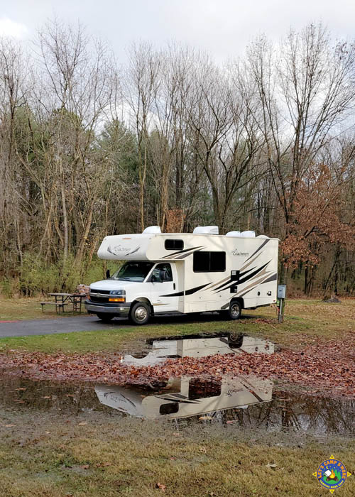 Coachman RV reflecting in a puddle of water